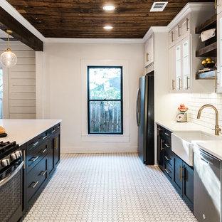 ダラスのミッドセンチュリースタイルのおしゃれなII型キッチン (エプロンフロントシンク、シェーカースタイル扉のキャビネット、黒いキャビネット、クオーツストーンカウンター、白いキッチンパネル、セラミックタイルのキッチンパネル、シルバーの調理設備、セラミックタイルの床) の写真