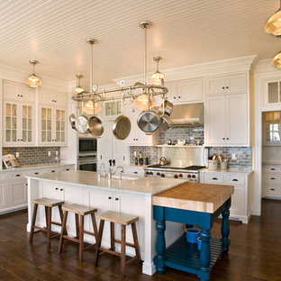 Inspiration for a large timeless u-shaped medium tone wood floor and brown floor kitchen remodel in Milwaukee with white cabinets, gray backsplash, subway tile backsplash, a farmhouse sink, shaker cabinets, marble countertops, stainless steel appliances and an island