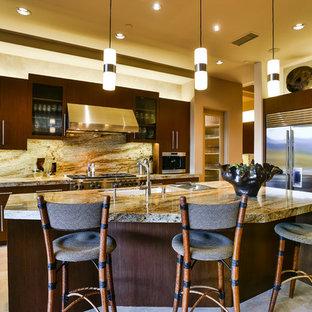 他の地域の巨大なコンテンポラリースタイルのおしゃれなキッチン (シングルシンク、フラットパネル扉のキャビネット、濃色木目調キャビネット、御影石カウンター、石スラブのキッチンパネル、シルバーの調理設備の、トラバーチンの床) の写真