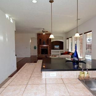 アルバカーキの大きいトラディショナルスタイルのおしゃれなキッチン (ダブルシンク、レイズドパネル扉のキャビネット、中間色木目調キャビネット、タイルカウンター、ベージュキッチンパネル、セラミックタイルのキッチンパネル、白い調理設備、セラミックタイルの床) の写真