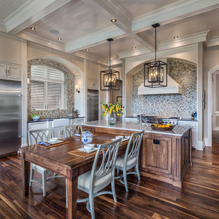 Traditional eat-in kitchen appliance - Example of a classic dark wood floor eat-in kitchen design in Other with white cabinets, granite countertops, multicolored backsplash, mosaic tile backsplash, stainless steel appliances, an island and beaded inset cabinets
