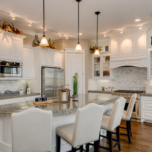 Traditional open concept kitchen ideas - Inspiration for a timeless l-shaped dark wood floor open concept kitchen remodel in Dallas with a double-bowl sink, raised-panel cabinets, white cabinets, granite countertops, beige backsplash, porcelain backsplash, stainless steel appliances and an island