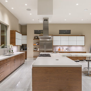 Large contemporary l-shaped open plan kitchen in Las Vegas with flat-panel cabinets, medium wood cabinets, solid surface benchtops, grey splashback, stainless steel appliances, ceramic floors and multiple islands.
