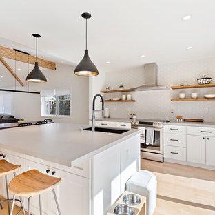 Idee per una cucina ad ambiente unico minimal con lavello sottopiano, ante in stile shaker, ante bianche, paraspruzzi bianco, elettrodomestici in acciaio inossidabile, parquet chiaro, un'isola, pavimento beige e top grigio