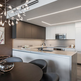 Contemporary u-shaped kitchen/diner in Miami with a submerged sink, flat-panel cabinets, white cabinets, metallic splashback, integrated appliances, a breakfast bar, grey floors and grey worktops.