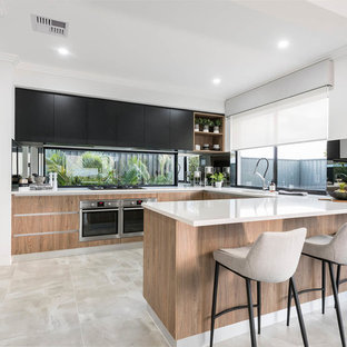 Design ideas for a large contemporary u-shaped kitchen in Perth with an undermount sink, flat-panel cabinets, black cabinets, quartz benchtops, stainless steel appliances, porcelain floors, a peninsula, beige floor and window splashback.