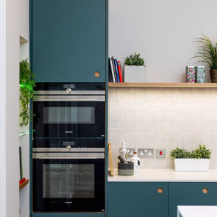 Photo of a mid-sized contemporary single-wall open plan kitchen in Other with an undermount sink, flat-panel cabinets, blue cabinets, quartzite benchtops, white splashback, stainless steel appliances, medium hardwood floors, with island, brown floor, white benchtop and porcelain splashback.