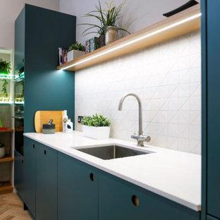 Offene, Einzeilige, Mittelgroße Moderne Küche mit Unterbauwaschbecken, flächenbündigen Schrankfronten, blauen Schränken, Quarzit-Arbeitsplatte, Küchenrückwand in Weiß, Küchengeräten aus Edelstahl, braunem Holzboden, Kücheninsel, braunem Boden, weißer Arbeitsplatte und Rückwand aus Porzellanfliesen in Sonstige