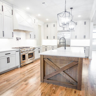 Inspiration for a large country l-shaped medium tone wood floor and brown floor open concept kitchen remodel in Dallas with a farmhouse sink, shaker cabinets, white cabinets, quartzite countertops, white backsplash, ceramic backsplash, stainless steel appliances, an island and white countertops