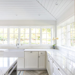 Large coastal eat-in kitchen appliance - Inspiration for a large coastal u-shaped porcelain tile and gray floor eat-in kitchen remodel in New York with a farmhouse sink, shaker cabinets, white cabinets, quartz countertops, white backsplash, subway tile backsplash, paneled appliances, an island and white countertops