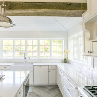 Large coastal eat-in kitchen ideas - Large beach style u-shaped porcelain tile and gray floor eat-in kitchen photo in New York with a farmhouse sink, shaker cabinets, white cabinets, quartz countertops, white backsplash, subway tile backsplash, paneled appliances, an island and white countertops