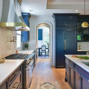 チャールストンの広いビーチスタイルのおしゃれなアイランドキッチン (青いキャビネット、クオーツストーンカウンター、グレーのキッチンパネル、パネルと同色の調理設備、淡色無垢フローリング、白いキッチンカウンター、折り上げ天井) の写真