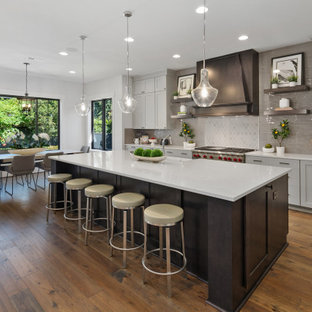 Mid-sized farmhouse eat-in kitchen inspiration - Example of a mid-sized cottage l-shaped medium tone wood floor and brown floor eat-in kitchen design in Seattle with a farmhouse sink, recessed-panel cabinets, gray cabinets, quartz countertops, gray backsplash, stainless steel appliances, an island and white countertops