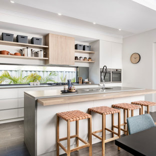 Design ideas for a mid-sized contemporary galley kitchen in Perth with an undermount sink, flat-panel cabinets, white cabinets, mirror splashback, stainless steel appliances, with island, grey floor and grey benchtop.