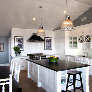Inspiration for a beach style l-shaped eat-in kitchen remodel in Orange County with a farmhouse sink, shaker cabinets, white cabinets, granite countertops, white backsplash and stainless steel appliances