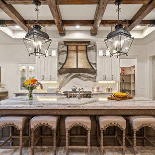 シンシナティの広いカントリー風おしゃれなキッチン (エプロンフロントシンク、白いキャビネット、クオーツストーンカウンター、パネルと同色の調理設備、トラバーチンの床、落し込みパネル扉のキャビネット、白いキッチンパネル、石スラブのキッチンパネル、ベージュの床、ベージュのキッチンカウンター) の写真