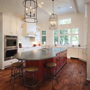 Réalisation d'une cuisine parallèle marine avec un évier encastré, des portes de placard rouges, une crédence blanche, un sol en bois brun, un îlot central et un sol marron.