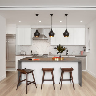 Mid-sized modern kitchen pictures - Kitchen - mid-sized modern galley light wood floor and beige floor kitchen idea in New York with flat-panel cabinets, white cabinets, concrete countertops, white backsplash, an island and gray countertops