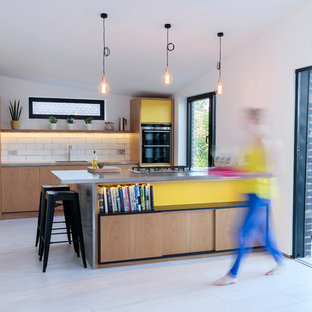 Photo of a medium sized scandinavian galley open plan kitchen in Other with stainless steel worktops and an island.