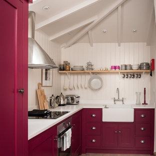 Geschlossene, Kleine Landhaus Küche in L-Form mit Landhausspüle, Schrankfronten im Shaker-Stil, roten Schränken, Laminat-Arbeitsplatte, Küchenrückwand in Weiß, Rückwand aus Holz, Küchengeräten aus Edelstahl, braunem Holzboden und beigem Boden in Cornwall