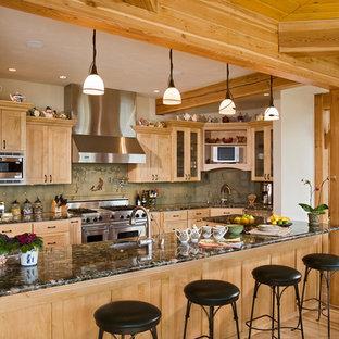 Foto de cocina en L, rural, grande, con fregadero bajoencimera, armarios estilo shaker, salpicadero gris, electrodomésticos de acero inoxidable, suelo de madera en tonos medios, una isla, encimera de granito, puertas de armario de madera clara y salpicadero de azulejos de cerámica
