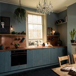 Mittelgroße Moderne Wohnküche ohne Insel mit integriertem Waschbecken, flächenbündigen Schrankfronten, blauen Schränken, Kupfer-Arbeitsplatte, Küchenrückwand in Orange, Elektrogeräten mit Frontblende, gebeiztem Holzboden und schwarzem Boden in Sonstige