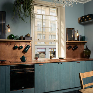 Mid-sized eclectic eat-in kitchen in London with an integrated sink, flat-panel cabinets, blue cabinets, copper benchtops, orange splashback, panelled appliances, painted wood floors, no island, black floor and orange benchtop.