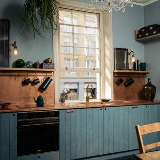 Modelo de cocina comedor ecléctica, de tamaño medio, sin isla, con fregadero integrado, armarios con paneles lisos, puertas de armario azules, encimera de cobre, salpicadero naranja, electrodomésticos con paneles, suelo de madera pintada, suelo negro y encimeras naranjas