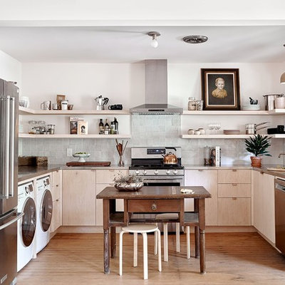 Example of a trendy u-shaped medium tone wood floor and brown floor kitchen design in Austin with an undermount sink, flat-panel cabinets, light wood cabinets, gray backsplash, mosaic tile backsplash, stainless steel appliances and an island