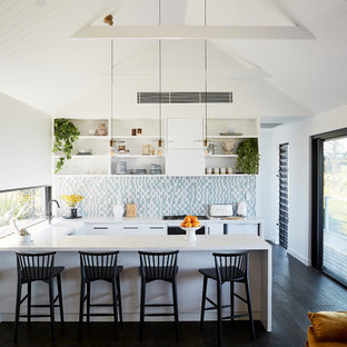 Beach style u-shaped open plan kitchen in Other with a farmhouse sink, flat-panel cabinets, white cabinets, multi-coloured splashback, panelled appliances, dark hardwood floors, a peninsula, black floor and white benchtop.