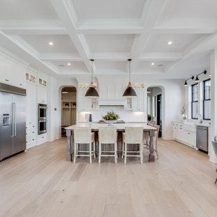 Diseño de cocina comedor campestre, grande, con fregadero sobremueble, puertas de armario blancas, salpicadero blanco, electrodomésticos de acero inoxidable, suelo de madera clara, una isla, suelo marrón y encimeras blancas