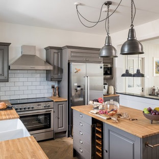 Inspiration for a nautical l-shaped kitchen/diner in Cornwall with a double-bowl sink, raised-panel cabinets, grey cabinets, wood worktops, white splashback, metro tiled splashback, stainless steel appliances, medium hardwood flooring, an island, brown floors and brown worktops.