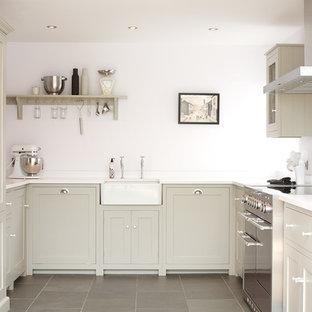 Bild på ett mellanstort lantligt u-kök, med en rustik diskho, skåp i shakerstil, grå skåp, vitt stänkskydd, glaspanel som stänkskydd, rostfria vitvaror och skiffergolv