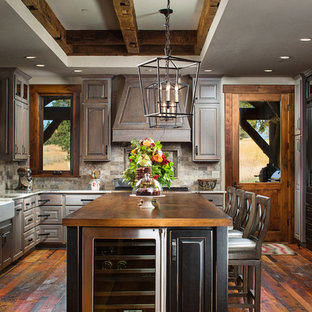 Inspiration pour une grande cuisine chalet en L avec un évier de ferme, un placard avec porte à panneau surélevé, des portes de placard en bois vieilli, une crédence marron, un électroménager encastrable, un sol en bois foncé, un îlot central et un plan de travail en cuivre.