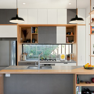 Mid-sized contemporary galley open plan kitchen in Melbourne with an undermount sink, flat-panel cabinets, window splashback, stainless steel appliances, with island, grey benchtop, white cabinets, medium hardwood floors and brown floor.