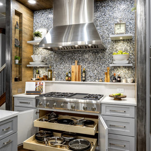 Design ideas for a large transitional open plan kitchen in Oklahoma City with a single-bowl sink, shaker cabinets, grey cabinets, quartz benchtops, grey splashback, porcelain splashback, stainless steel appliances, medium hardwood floors, with island and brown floor.