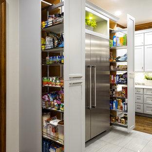 オクラホマシティの広いトランジショナルスタイルのおしゃれなキッチン (シェーカースタイル扉のキャビネット、グレーのキャビネット、シルバーの調理設備、無垢フローリング、茶色い床) の写真