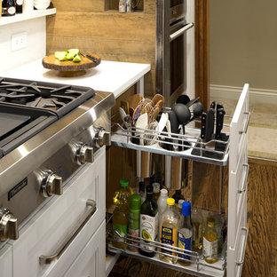 オクラホマシティの広いトランジショナルスタイルのおしゃれなアイランドキッチン (シングルシンク、シェーカースタイル扉のキャビネット、グレーのキャビネット、クオーツストーンカウンター、グレーのキッチンパネル、磁器タイルのキッチンパネル、シルバーの調理設備、無垢フローリング、茶色い床) の写真