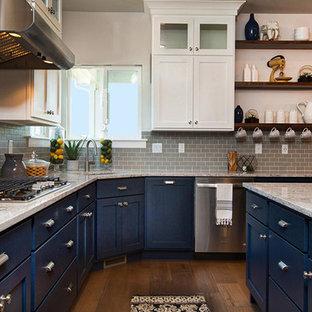 Klassische Wohnküche mit Einbauwaschbecken, flächenbündigen Schrankfronten, blauen Schränken, Quarzwerkstein-Arbeitsplatte, Küchengeräten aus Edelstahl, dunklem Holzboden, Kücheninsel, Küchenrückwand in Grau und Rückwand aus Metrofliesen in Salt Lake City