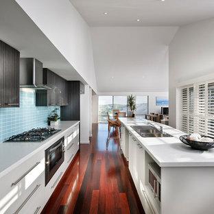 パースの中くらいのコンテンポラリースタイルのおしゃれなキッチン (ダブルシンク、フラットパネル扉のキャビネット、白いキャビネット、シルバーの調理設備、クッションフロア) の写真