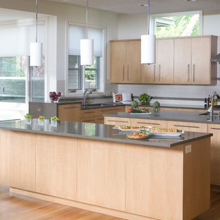 Photo of a large contemporary eat-in kitchen in Boise with an undermount sink, flat-panel cabinets, light wood cabinets, quartzite benchtops, white splashback, ceramic splashback, stainless steel appliances, medium hardwood floors and multiple islands.