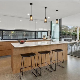 Photo of a contemporary galley open plan kitchen in Melbourne with flat-panel cabinets, medium wood cabinets, window splashback, concrete floors, with island, grey floor and white benchtop.