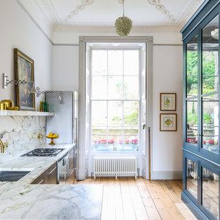 他の地域の中サイズのトランジショナルスタイルのおしゃれなキッチン (アンダーカウンターシンク、フラットパネル扉のキャビネット、ステンレスキャビネット、大理石カウンター、マルチカラーのキッチンパネル、大理石の床、シルバーの調理設備の、淡色無垢フローリング、アイランドなし、ベージュの床) の写真