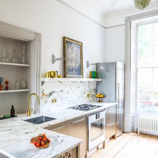 Klassisk inredning av ett mellanstort kök, med släta luckor, skåp i rostfritt stål, marmorbänkskiva, en undermonterad diskho, flerfärgad stänkskydd, stänkskydd i marmor, rostfria vitvaror, ljust trägolv och gult golv