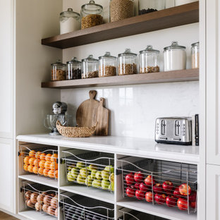 This is an example of a traditional kitchen pantry in Salt Lake City with beige cabinets, white splashback and white benchtop.