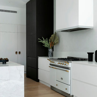 Photo of a large contemporary galley open plan kitchen in Perth with white cabinets, marble benchtops, white splashback, stainless steel appliances, medium hardwood floors, with island, white benchtop, flat-panel cabinets and beige floor.