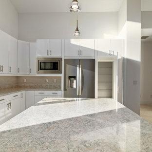 他の地域の広いミッドセンチュリースタイルのおしゃれなキッチン (フラットパネル扉のキャビネット、白いキャビネット、クオーツストーンカウンター、ガラスタイルのキッチンパネル、シルバーの調理設備、磁器タイルの床、白い床、ターコイズのキッチンカウンター) の写真