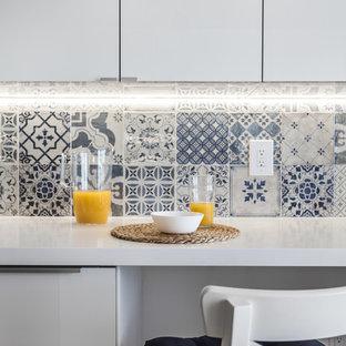 マイアミのビーチスタイルのおしゃれなキッチン (アンダーカウンターシンク、フラットパネル扉のキャビネット、白いキャビネット、珪岩カウンター、白いキッチンパネル、セラミックタイルのキッチンパネル、シルバーの調理設備、クッションフロア、ベージュの床) の写真