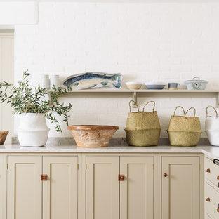 Offene, Mittelgroße Urige Küche in L-Form mit Landhausspüle, Schrankfronten im Shaker-Stil, beigen Schränken, Quarzit-Arbeitsplatte, Küchenrückwand in Weiß, Rückwand aus Backstein, bunten Elektrogeräten, braunem Holzboden und Kücheninsel in Sonstige