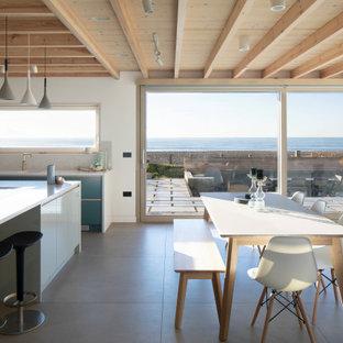 Diseño de cocina en L, moderna, abierta, con armarios con paneles lisos, puertas de armario azules, salpicadero blanco, salpicadero de losas de piedra, una isla, suelo gris y encimeras blancas